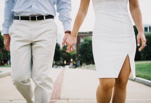 couple in white holding hands