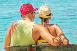 couple with hats by the sea