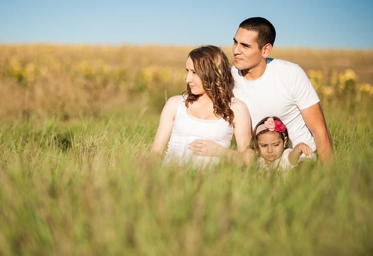 couple with kid in grass