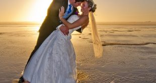 newly weds kissing at sunset