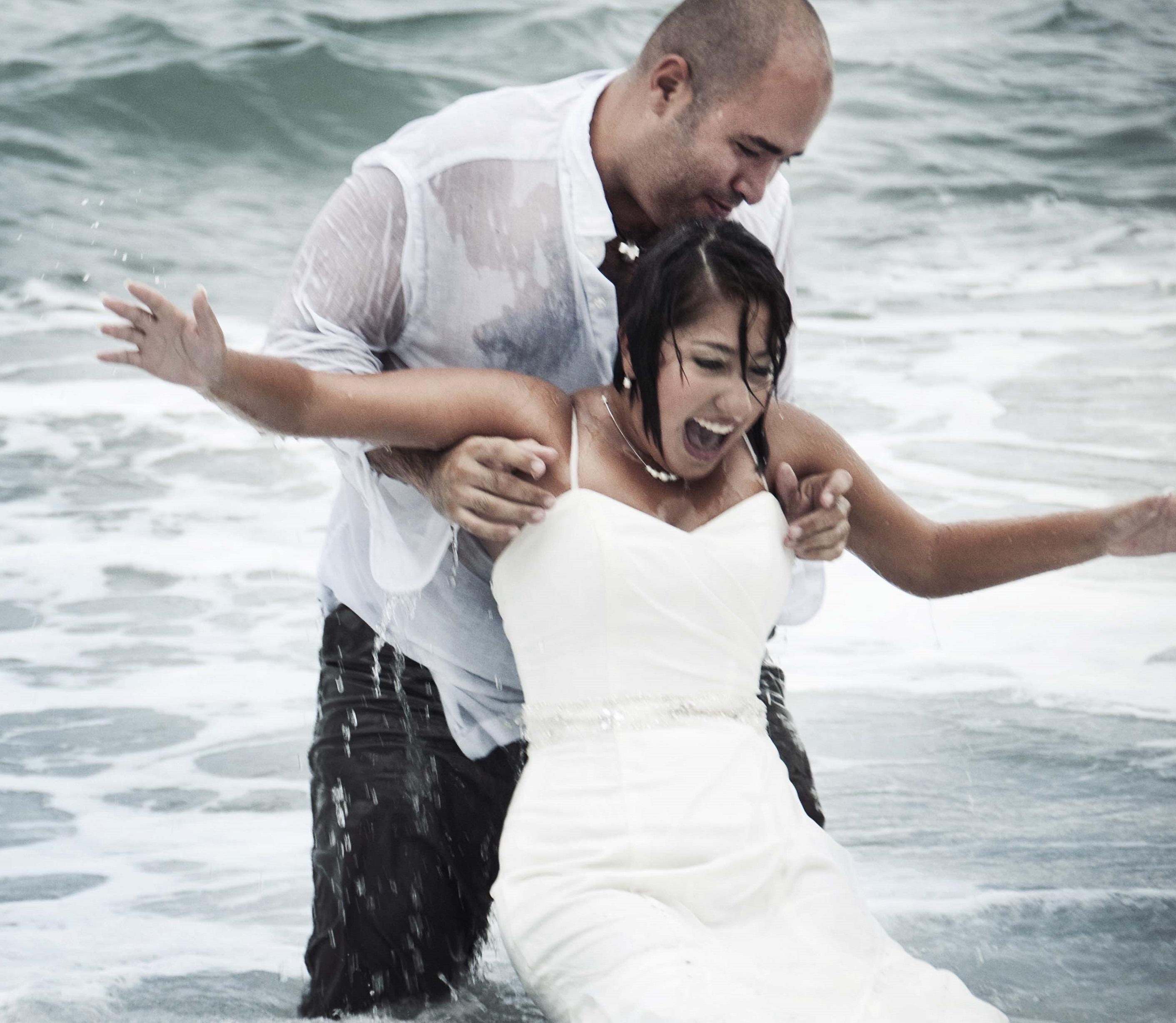 wedded couple having fun in water
