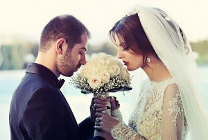 wedded couple smelling flowers